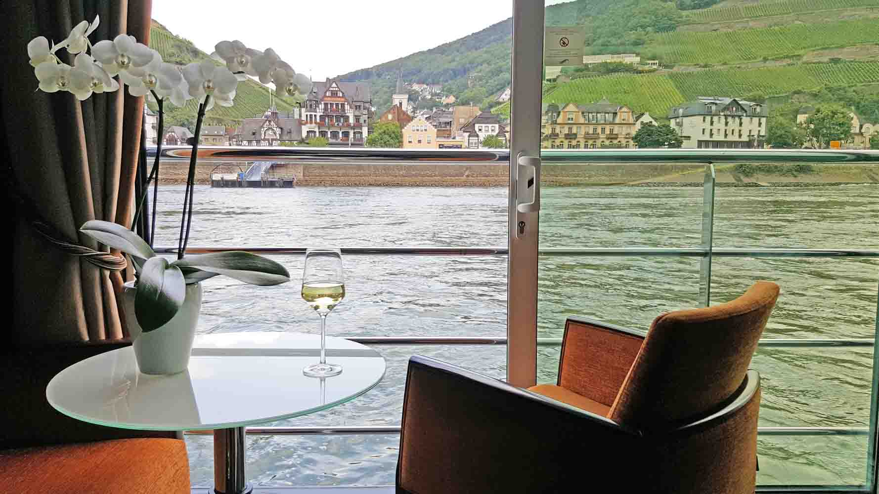 glass of wine on table with river cruising