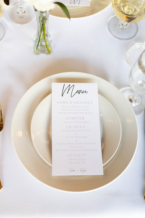 Place setting with white linen, white plates, and a white menu on the plates.