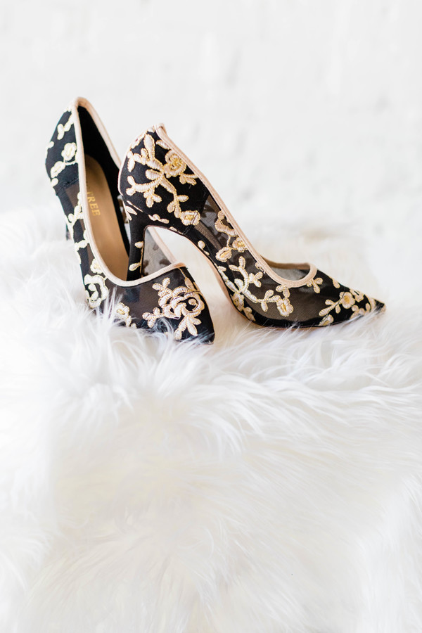 Black wedding shoes with white designs on them.