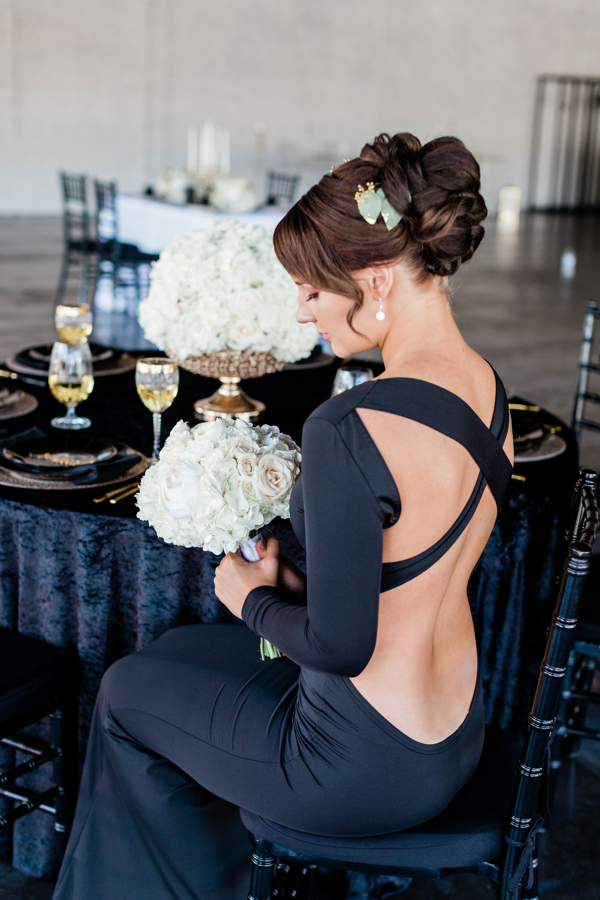 Bride changed into a sleek black dress holding a white bouquet, sitting at a table with a black linen.