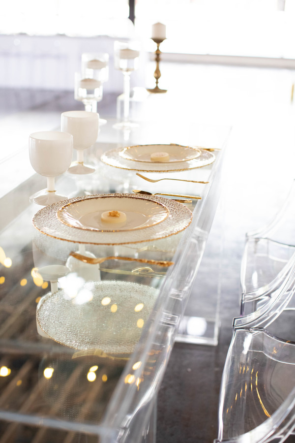 Clear table with white plates and gold trim.