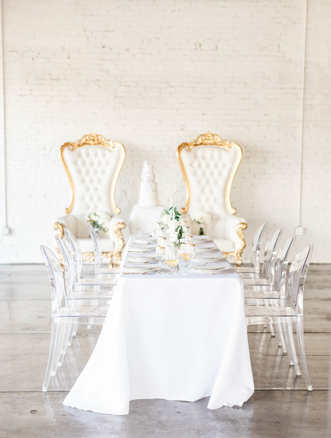 White wedding tablescape with a white linen, clear chairs, and white plates with pops of greenery.