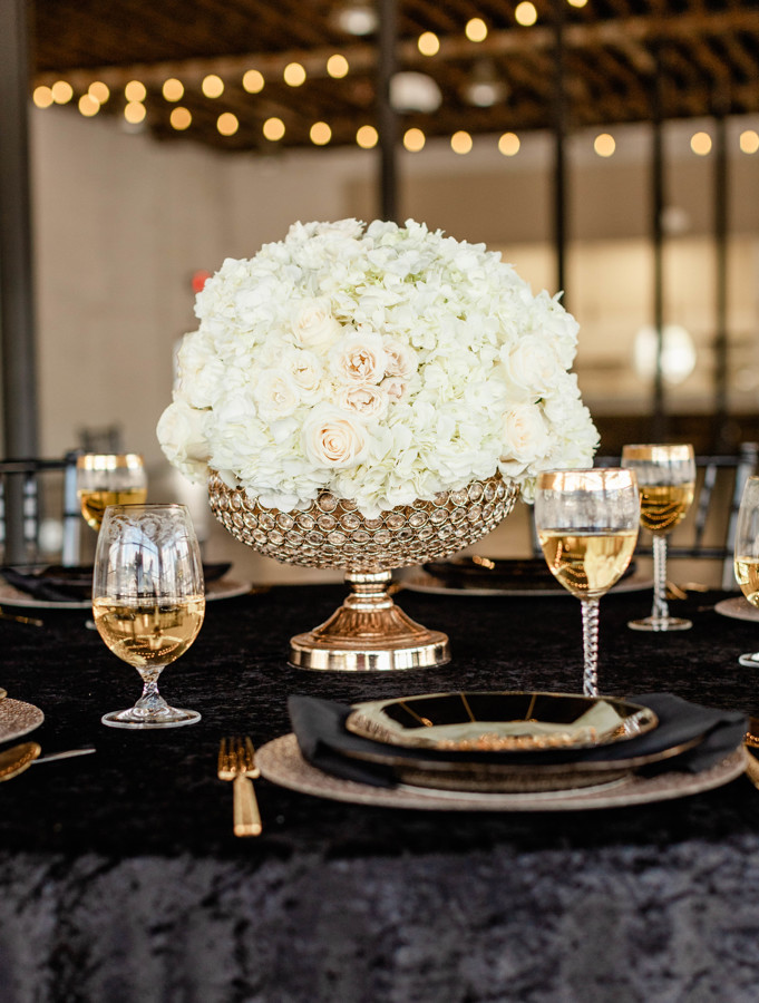 Large white wedding centerpiece in a gold holder on top of a table with a black velvet linen.