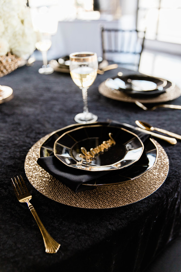 Table with black linen, gold charger, and black and gold plates. A gold acrylic nametag on top of the plate.