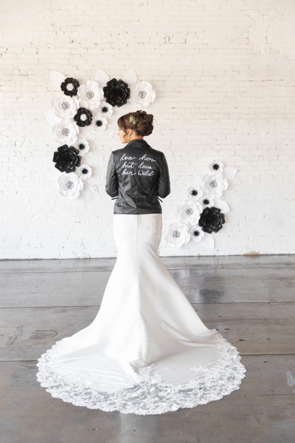 Bride in black leather jean jacket with black and white paper flowers on the wall behind her.