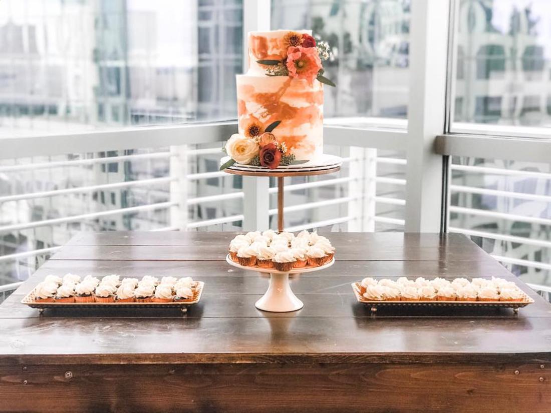 2 tiered coral orange wedding cake with fresh flowers