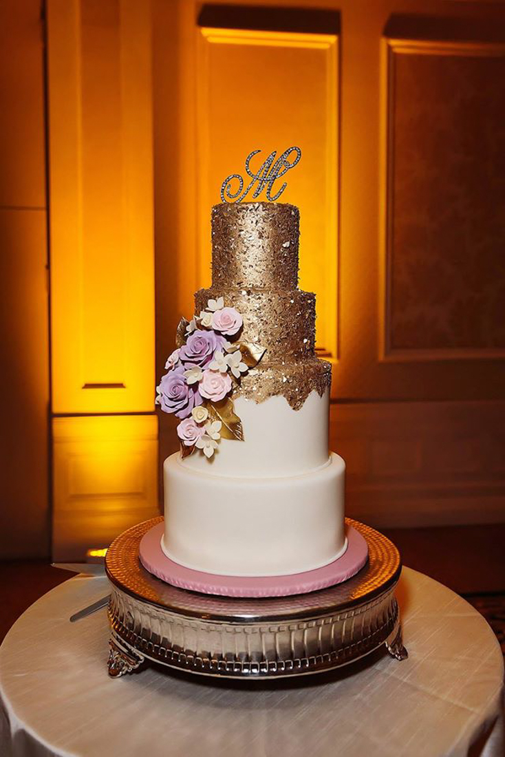 4 tiered wedding cake with the top two layers covered in sparkly gold. Purple sugar flowers added.