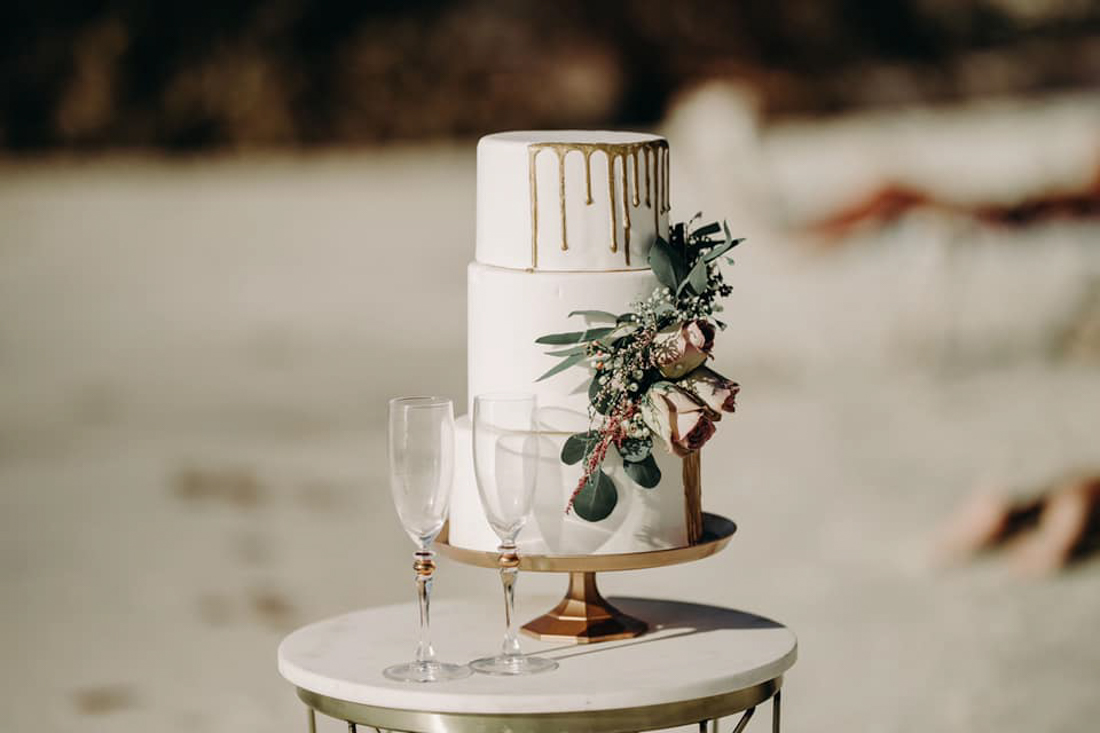 white 3 tiered wedding cake with gold drip roses added to the side of the cake.