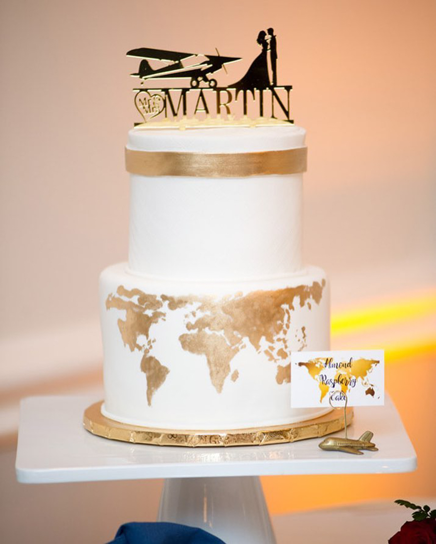 Travel themed wedding cake with gold flakes on bottom to create the globe, with an airplane cake topper.