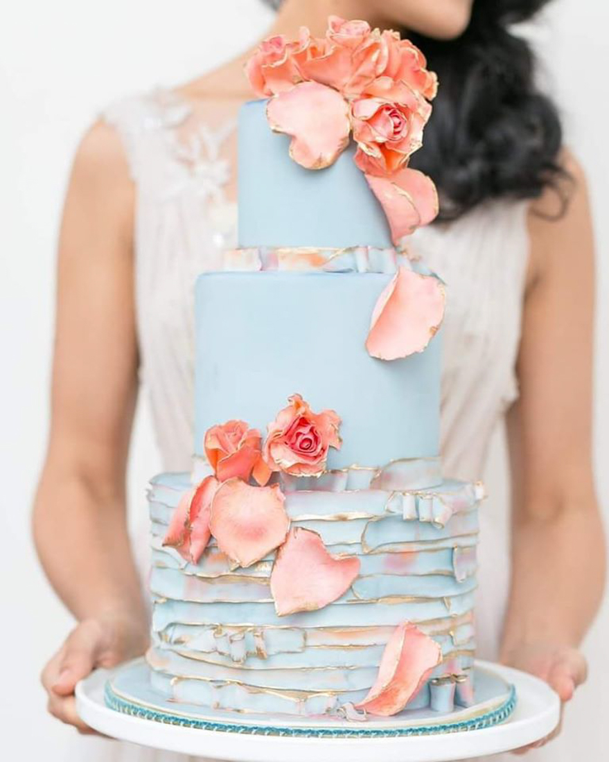 Pale blue 3 tiered wedding cake with hand painted ruffles and peach sugar flowers