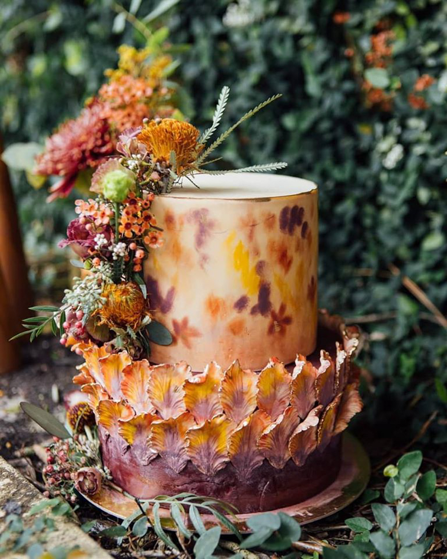 Purple and orange ombre wedding cake with painted purple and yellow sugar petals. Top layer is hand painted. Fall flowers are placed on the side.