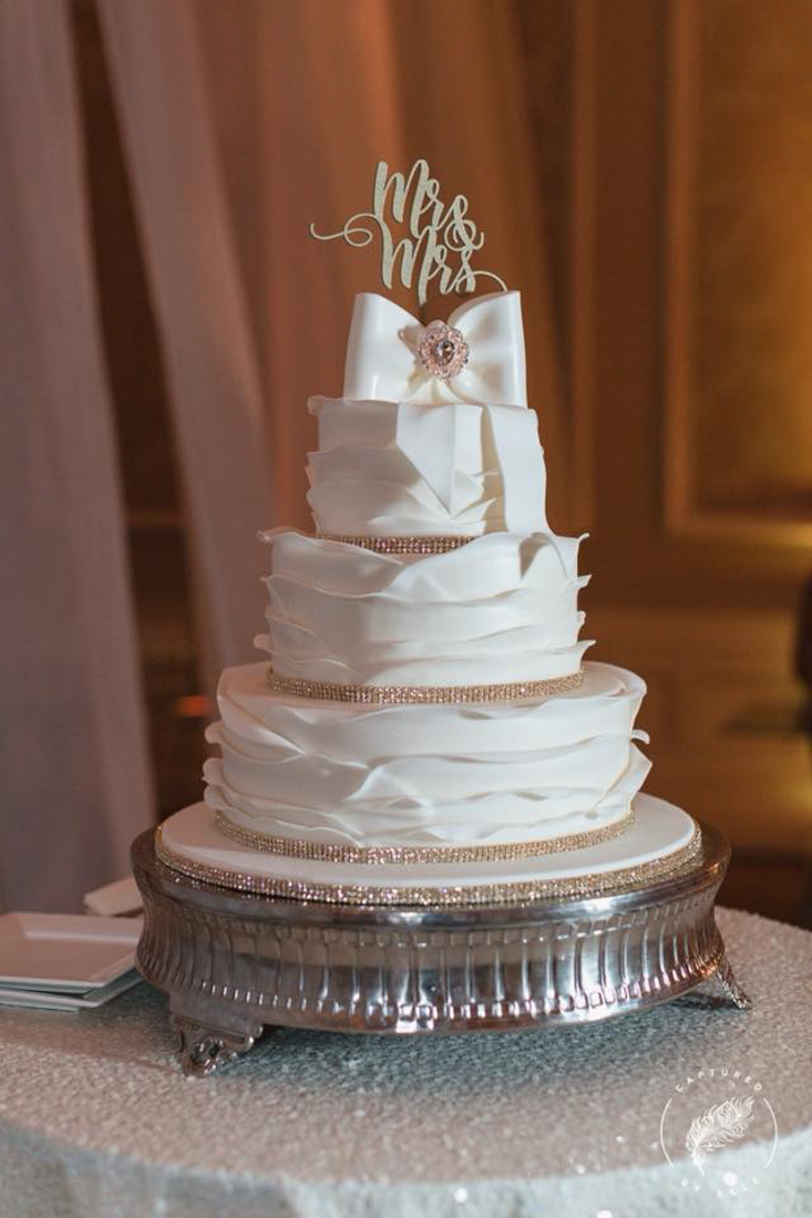 4 tiered white ruffled wedding cake with a fondant bow on top. Layers separated by pink jeweled ribbon.