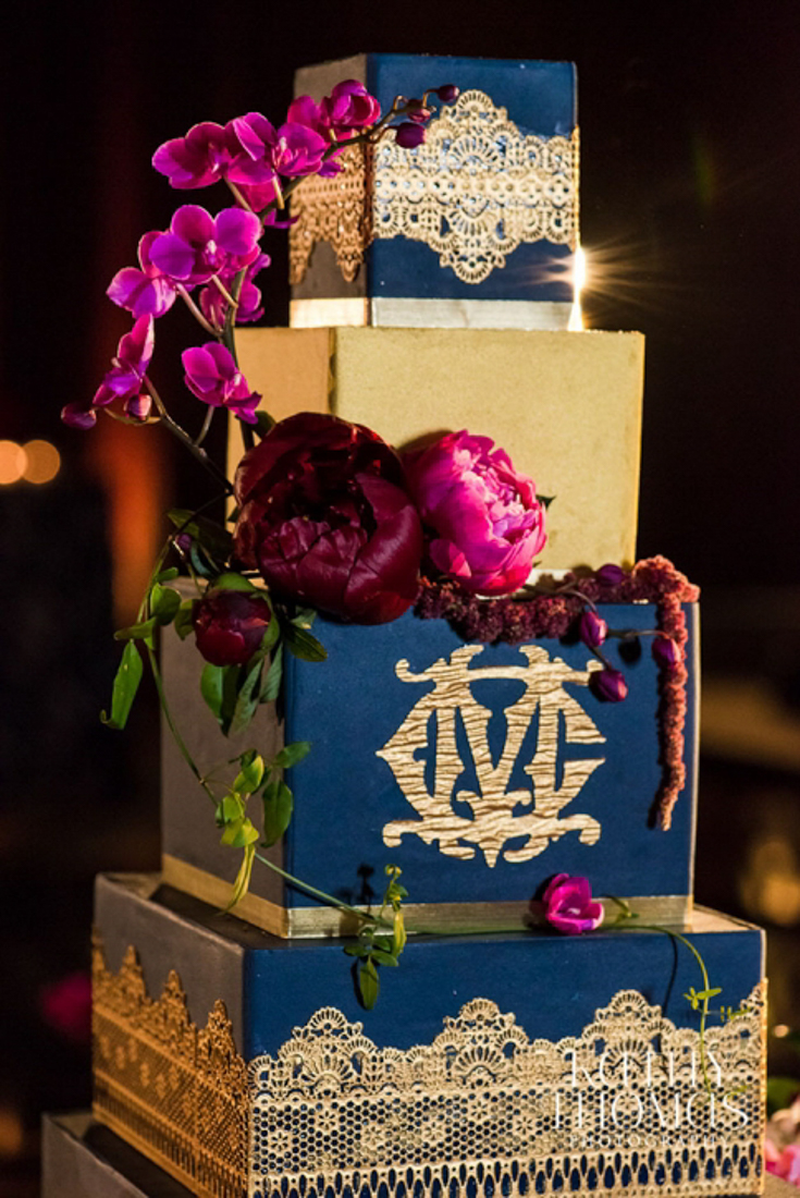 4 tiered navy blue and gold wedding cake with fuschia flowers