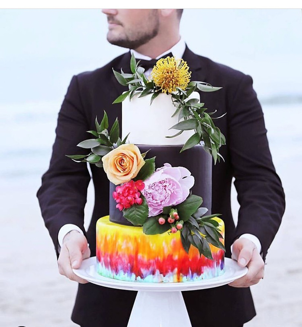 Colorful 3 tiered wedding cake with one tie dye red and yellow layer, a black layer, and a white layer. Finished with fresh flowers.