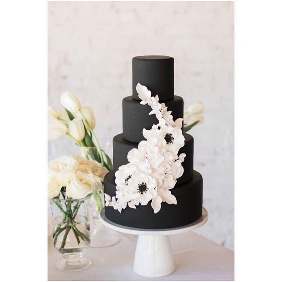 Black 4 tiered wedding cake with white sugar flowers on it.