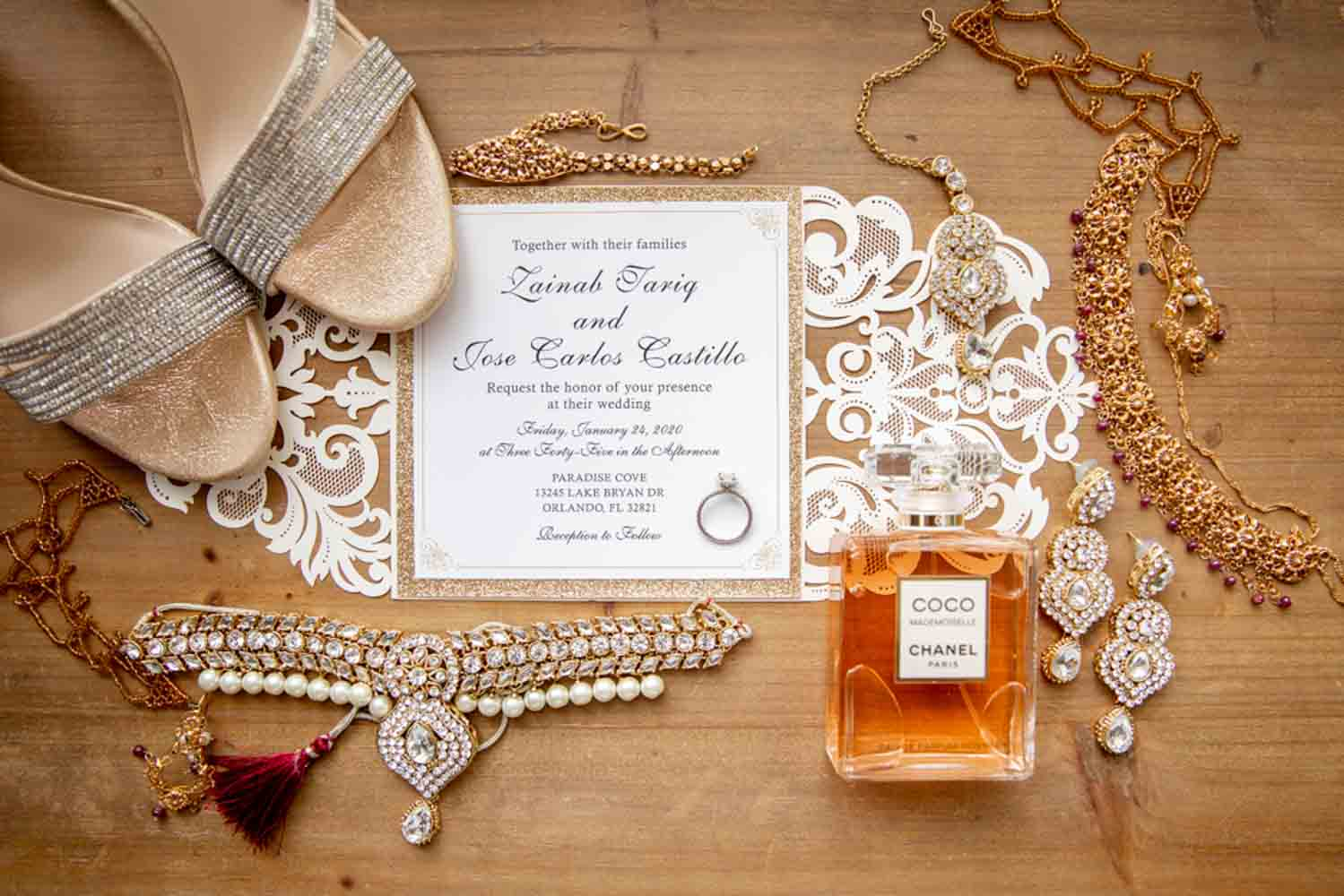 gold toned bridal accessories on white lace wedding invitation