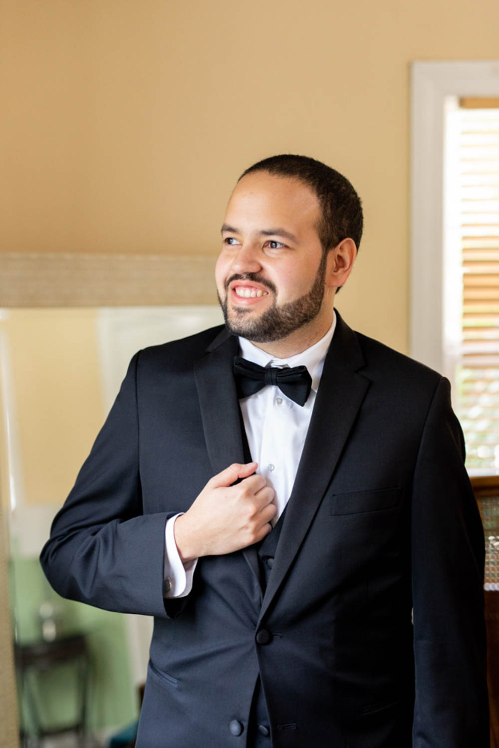 groom in black tux smiling while looking out of window
