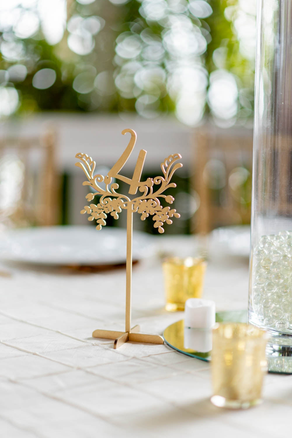 gold laser cut table numbers on guest tables for wedding