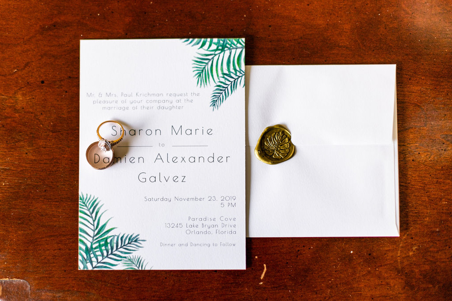 Palm leave wedding invitation with wedding bands and engagement ring