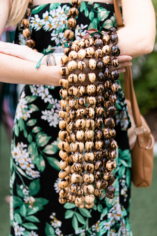 woman holding kukui nut necklaces for Paradise Cove wedding