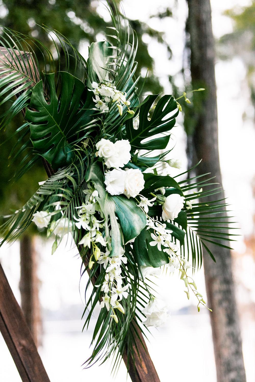 tropical floral arrangement on wedding ceremony arch