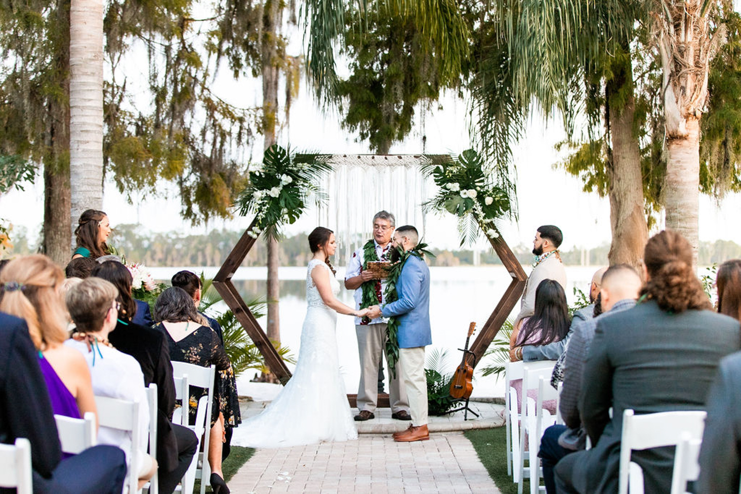 bride and groom in front of hexagon wedding ceremony backdrop with tropical florals