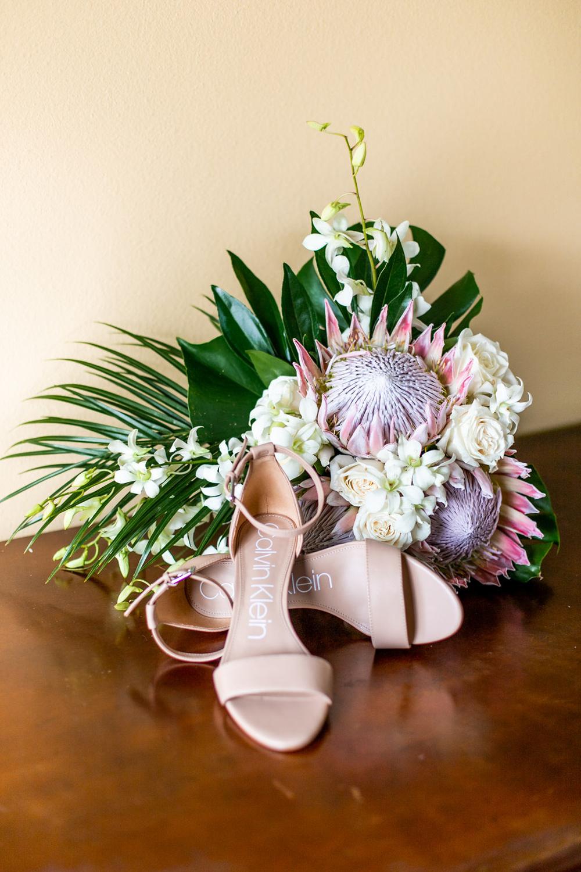 Tropical bridal bouquet next to nude tone bridal shoes