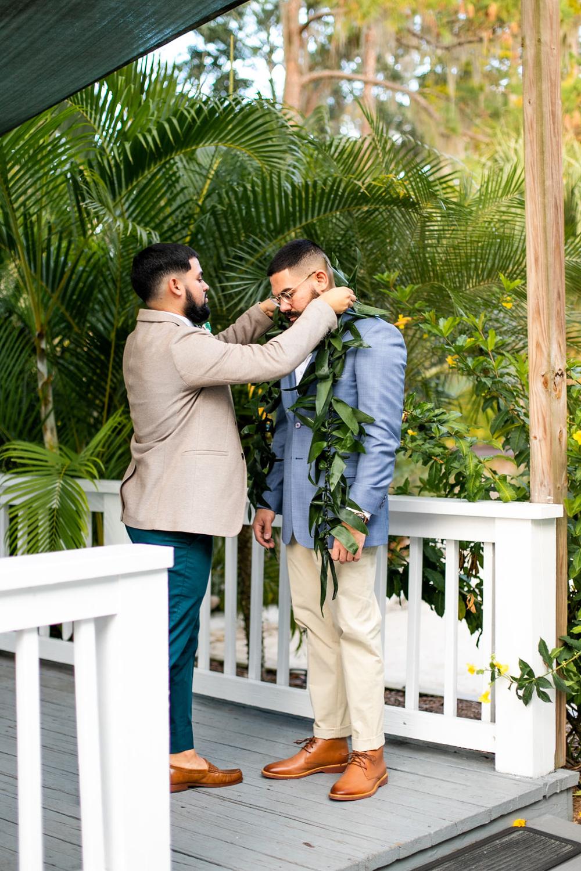 best man placing Hawaiian lei on groom for wedding day