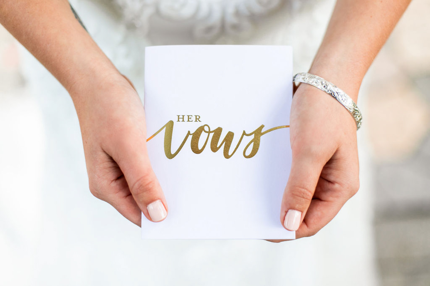 bride hold white vow book with gold writing