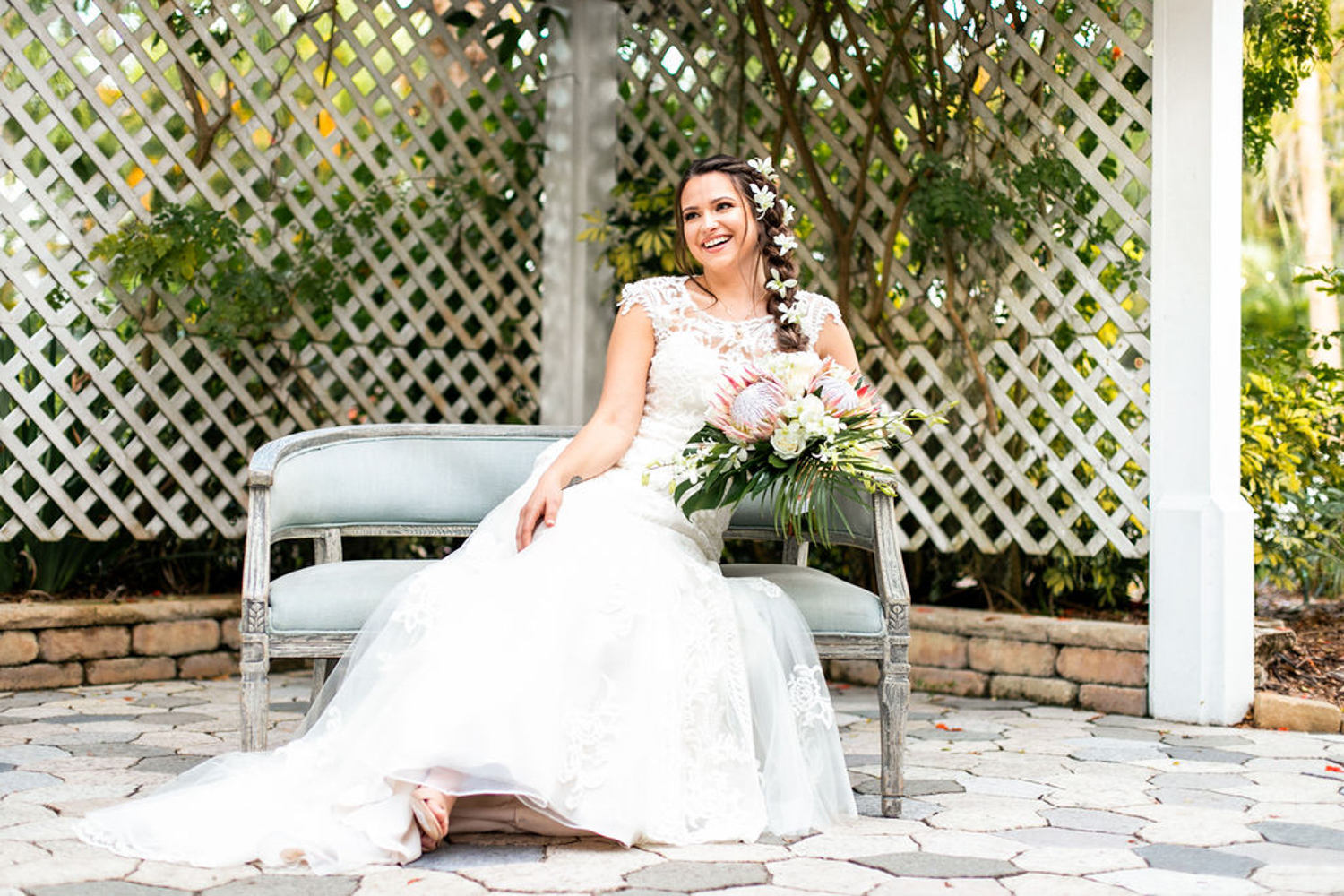 bride smiling on settee before wedding ceremony