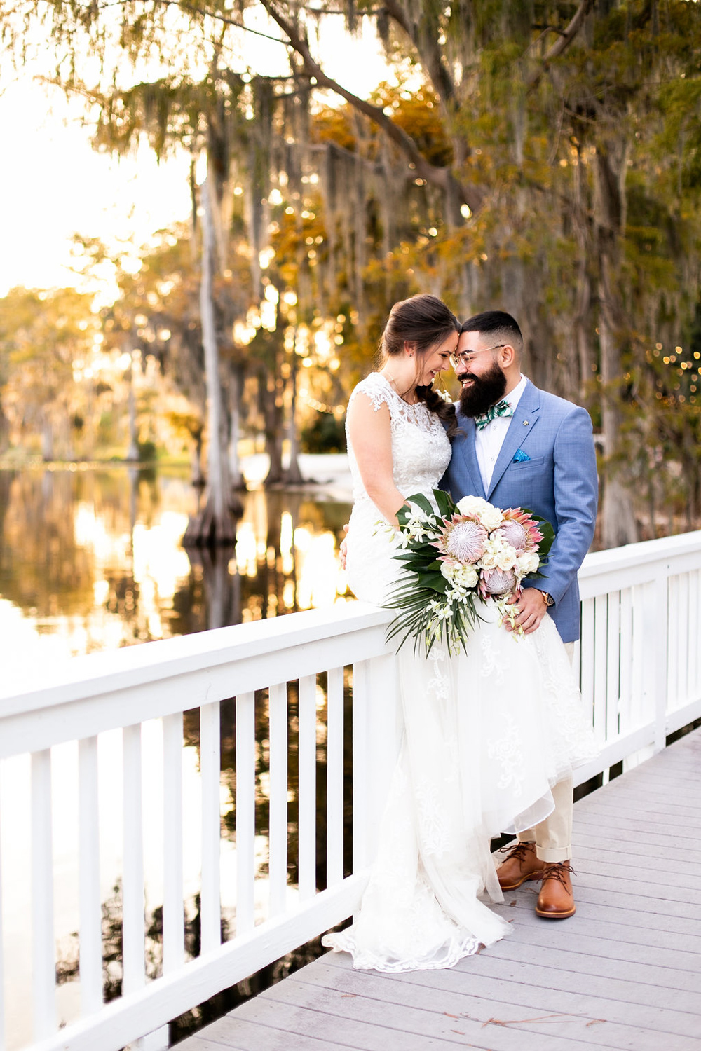 bride sitting on deck rail with groom next to her