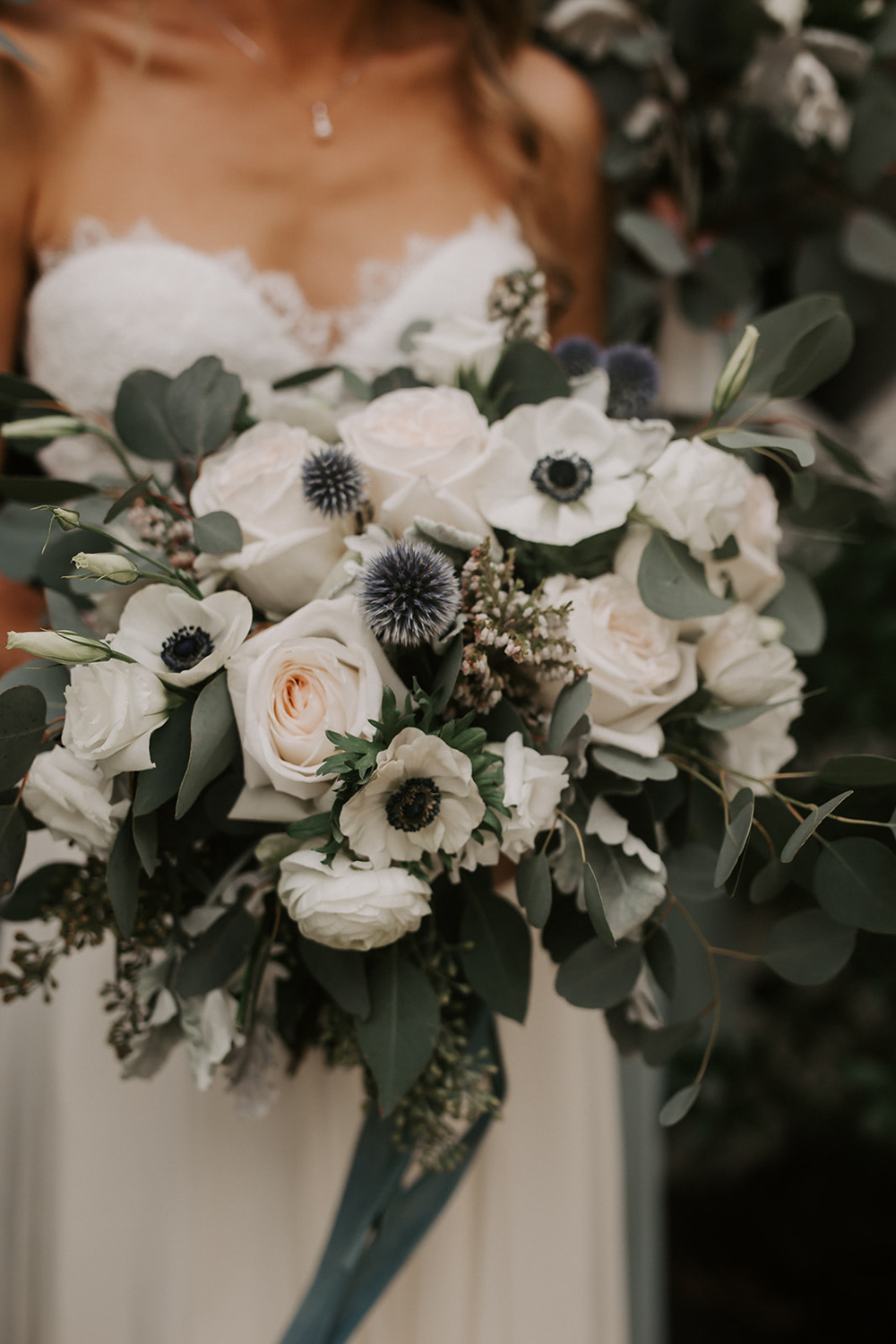 bride bouquet with white anemones and blue thistles