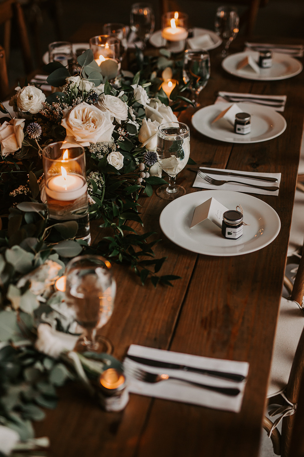 wedding reception table with greenery and floating candles