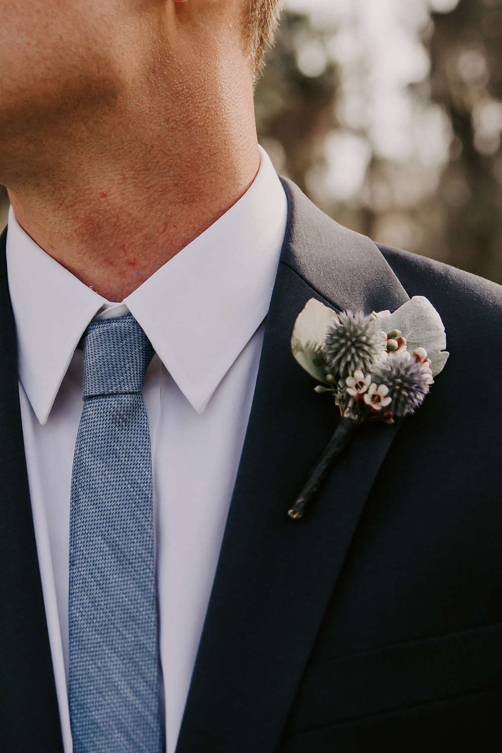 blue thistle boutonniere on navy suit jacket