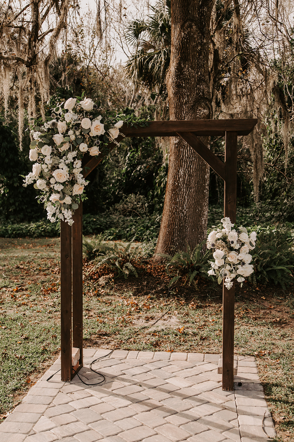 rustic wood ceremony arch with large white and greenery floral arrangement