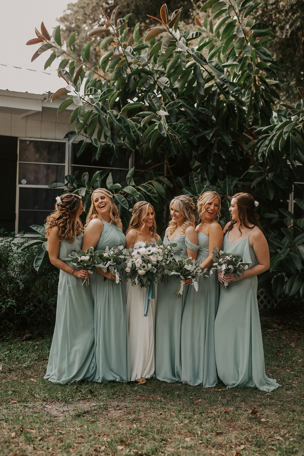 bridesmaids in sage dresses laughing with bride