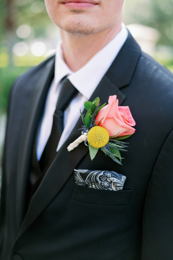 coral rose boutonniere with yellow flower
