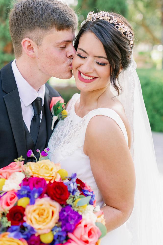 bride smiling as groom kisses check