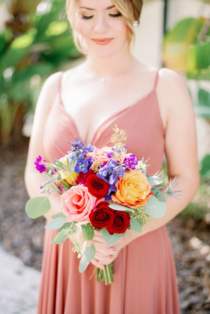 bridesmaid in mauve dress holding colorful bridesmaid bouquet
