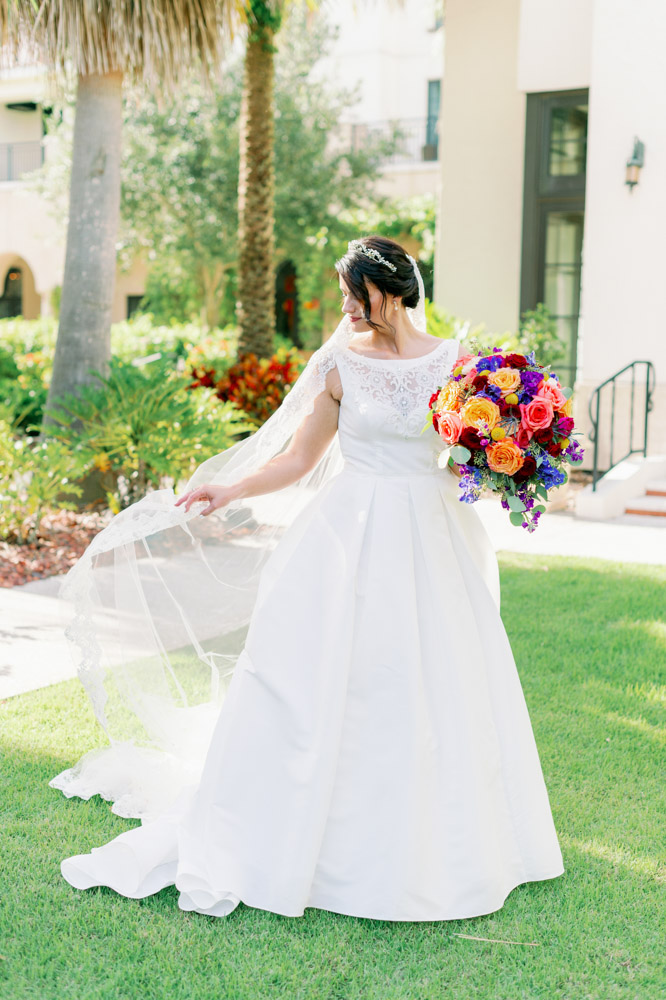 bride holding veil and bouquet in courtyard