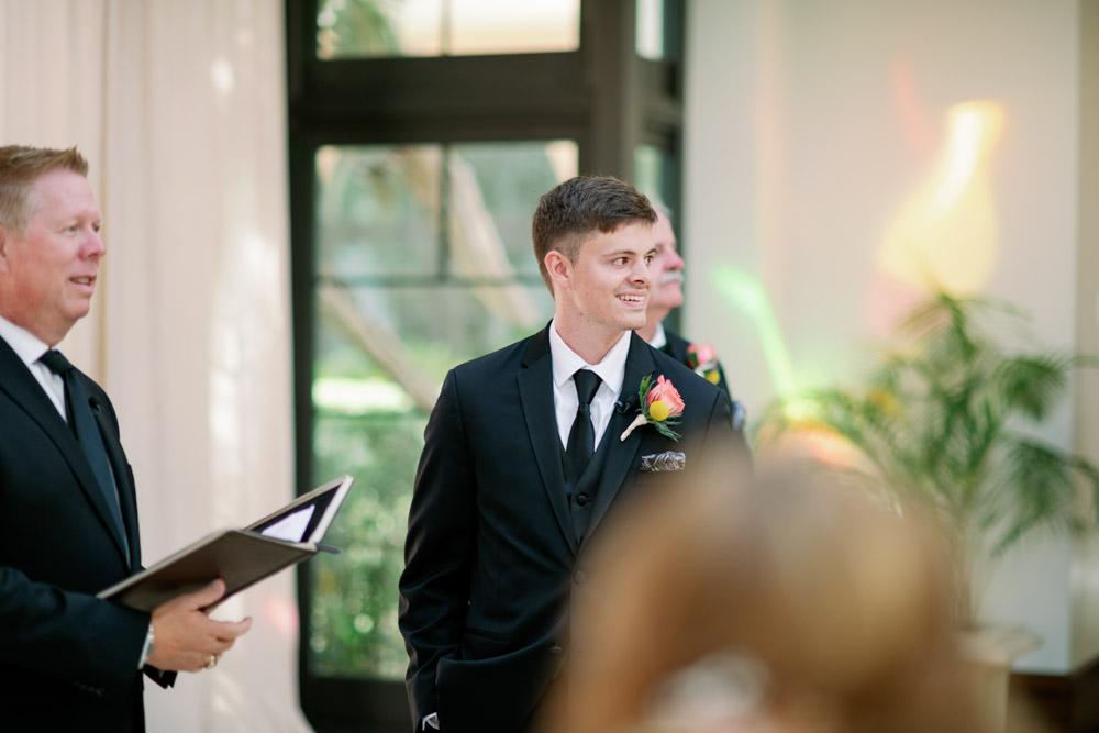groom smiling watching bride walk up aisle