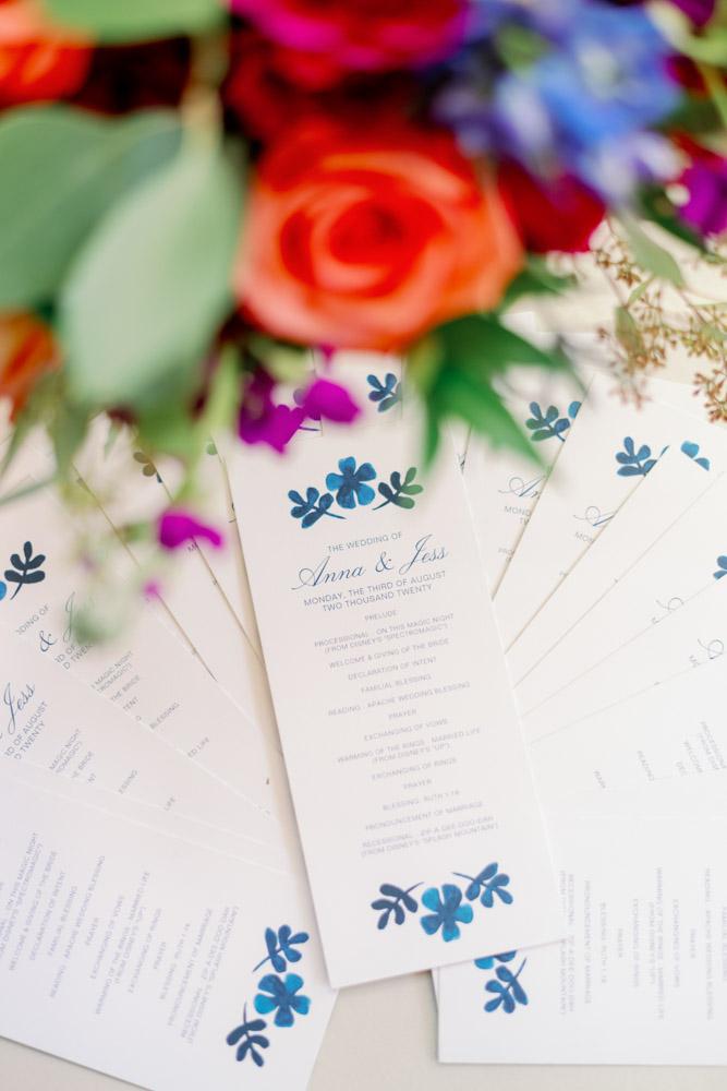blue floral design wedding ceremony cards on table