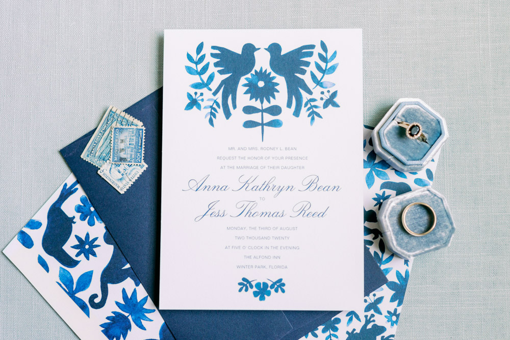 blue wedding invitation with engagement ring in blue jewelry box