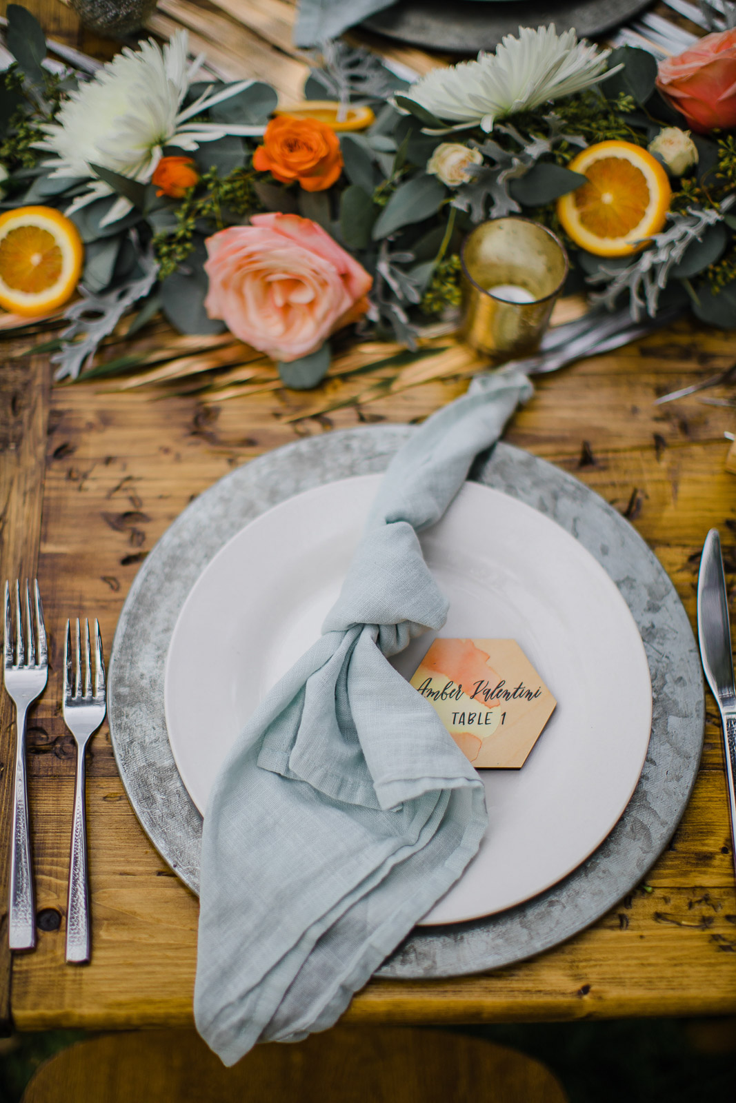 dusty blue napkin on white plate with orange watercolor hexagon placecard