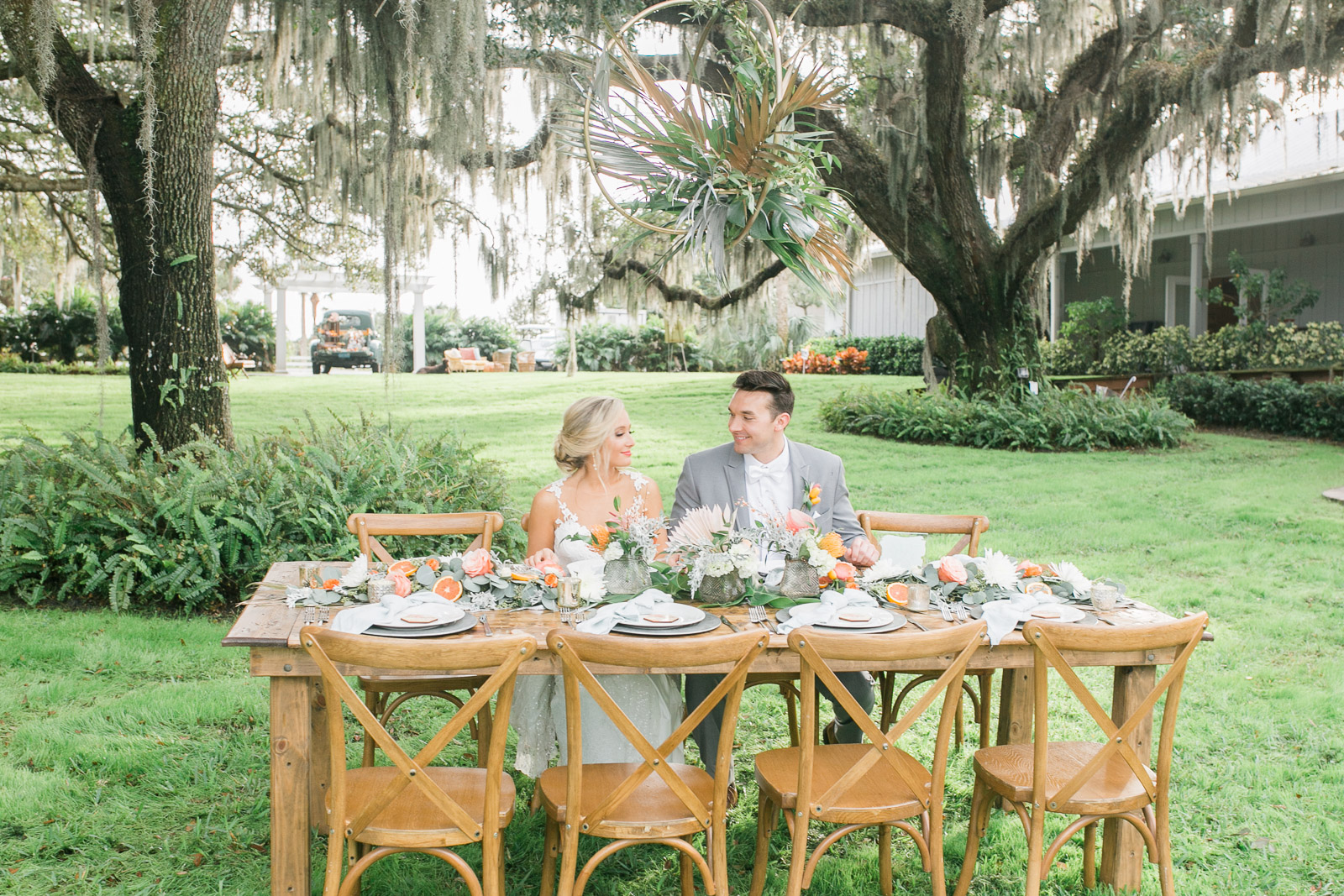 bride and groom sitting at outdoor reception table
