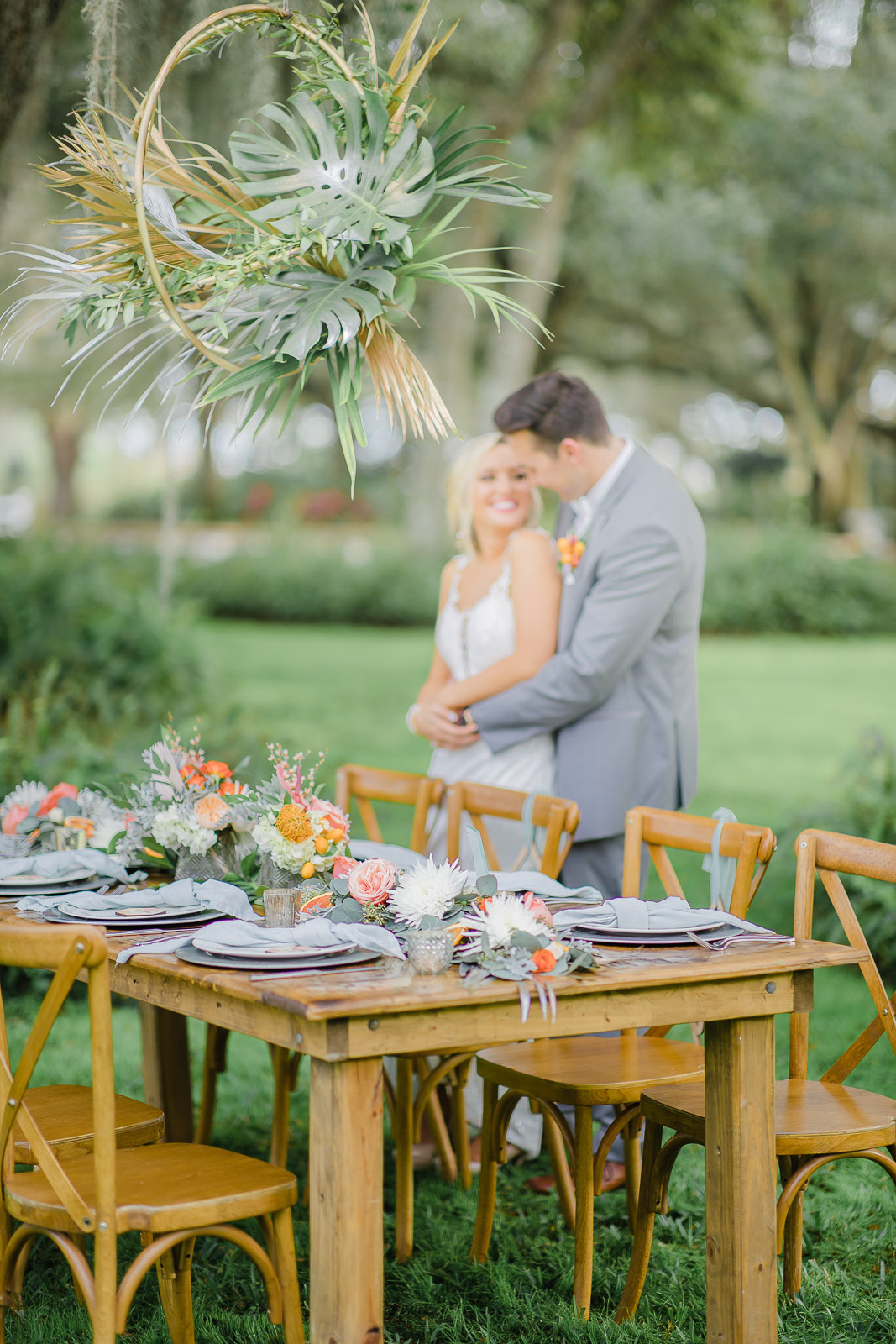 Rustic wedding reception farmtable with citrus centerpieces and hanging tropical arrangement