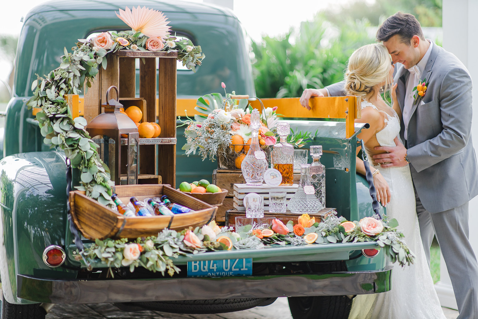 Bride and groom leaning on vintage truck