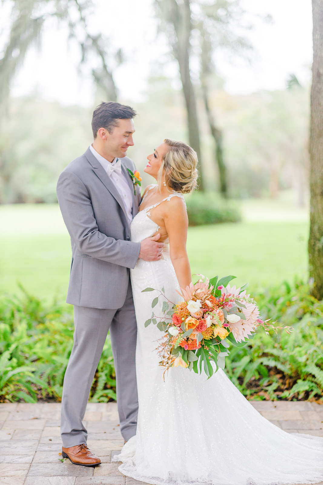 bride holding large tropical bouquet and groom in gray suit