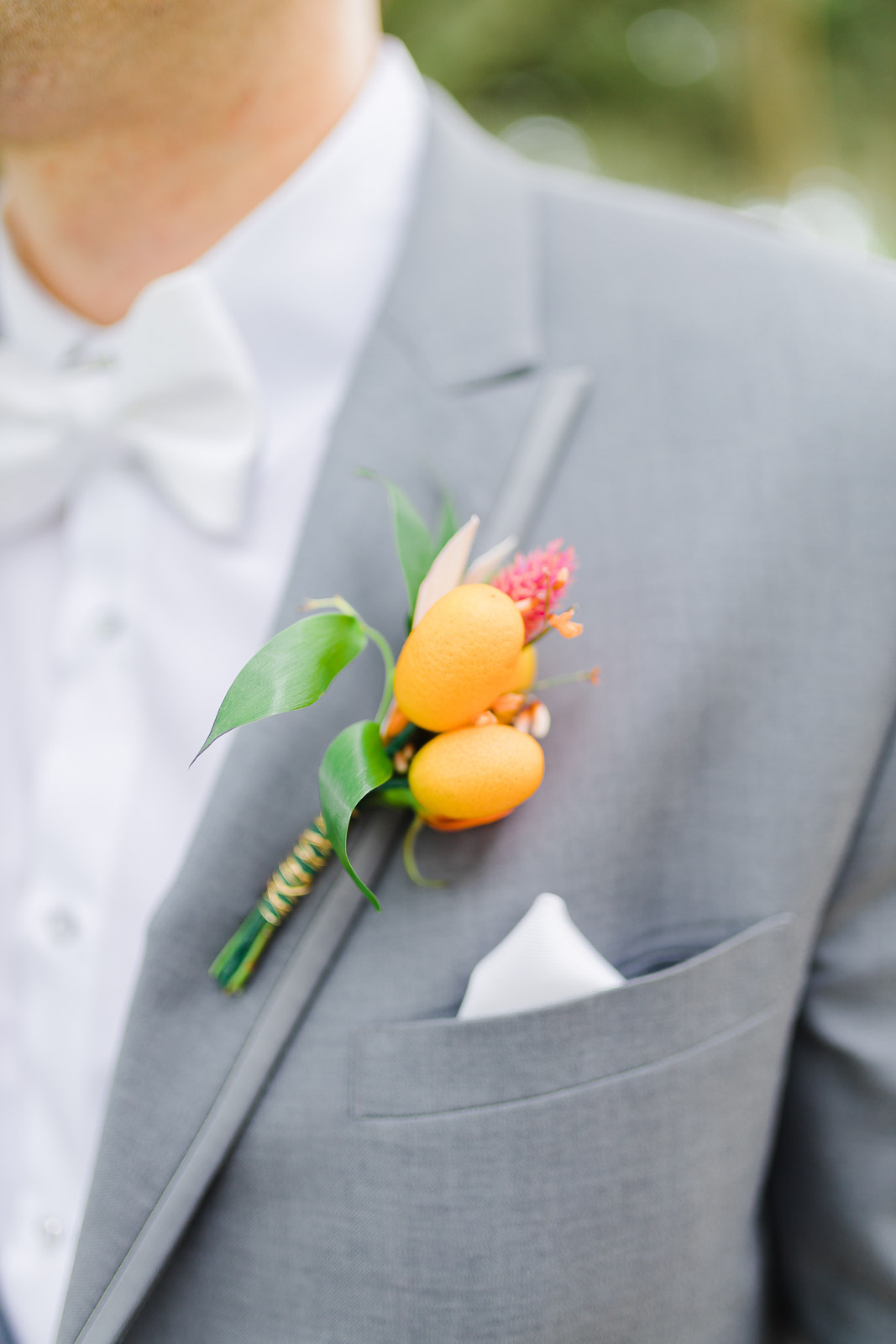 Citrus boutonniere on gray jacket