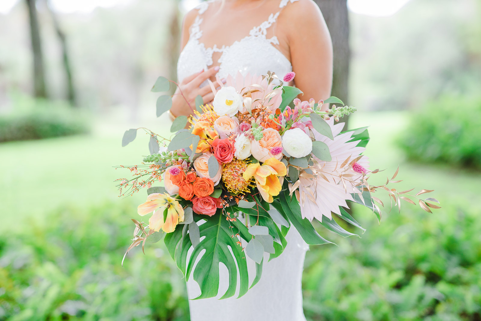bride holding large citrus inspired wedding bouquet with tropical colors and flowers